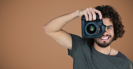 Millennial man with camera against brown background
