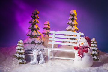 Winter picture. A bench with a snowman.