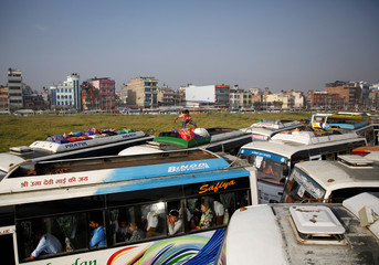 A man loads luggage on top of a long distance bus heading to the village during Dashain in Kathmandu