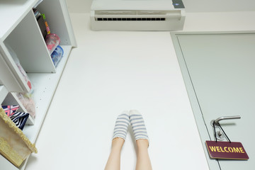 Slim Legs. Woman's Legs in Striped Yellow socks Near Door with Label Welcome on White Wall at Home Great for Any Use.