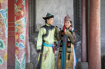 mongolian couple in traditional 13th century style outfit walking near old temple