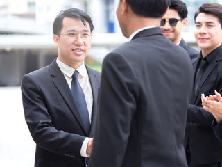 Business congratulations concept, middle age of asian businessman shaking hands with boss, manager for successful in business