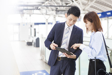 Business couple speaks while using tablet at the station home