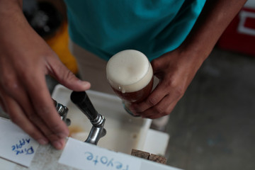 A worker drafts a glass of craft beer from a pump in a beer garden at the garage of Social Club brewery in Caracas
