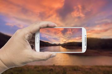 Hand holding smart phone taking photo