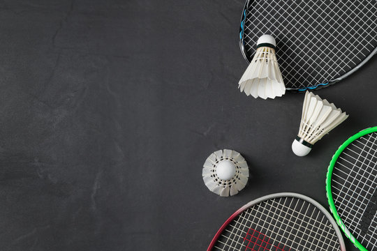 Shuttlecocks and badminton racket on black background.