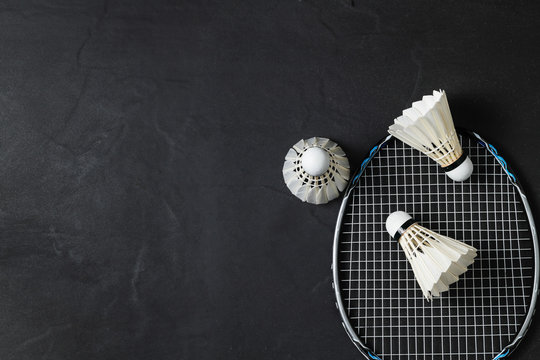 Shuttlecocks and badminton racket on black background