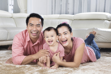 Cheerful family lying on the carpet
