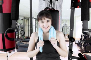 Arabian woman sitting on gym equipment