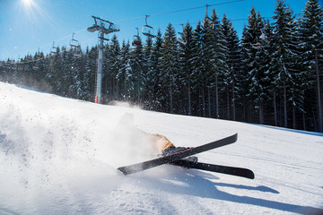 Skier falling on the slope on fresh powder snow at winter resort adventure extreme adrenaline active lifestyle concept