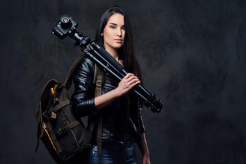 Brunette female photographer holds professional camera on a tripod.