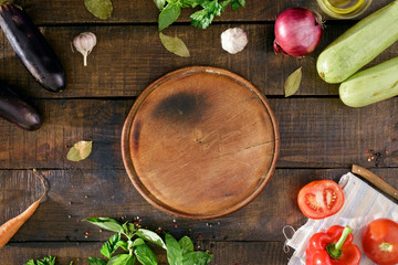 Around the round kitchen board different vegetables, top view