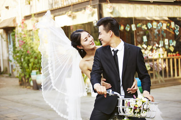 romantic asian newly-wed riding a bicycle