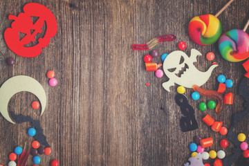 Trick and treat - colorful halloween candies border on wood with copy space, retro toned