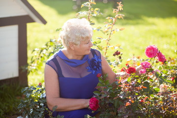 Elegant elderly woman outdoors with roses