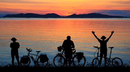 Silhouette man and bike relaxing with blurry sunrise background.