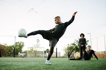 Player kicking soccer ball on field