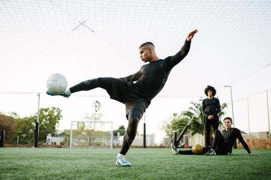 Man kicking soccer ball on field