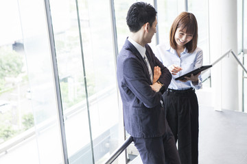 Business couple talking while touching the tablet