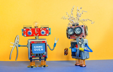 Industry 4.0 service repair maintenance concept. Creative design robotic toys, adjustable spanner silver pliers tools. Funny face robot, message Game over. Yellow blue background