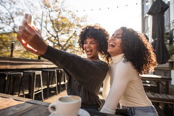 Two young women having fun taking a selfie Fotoväggar