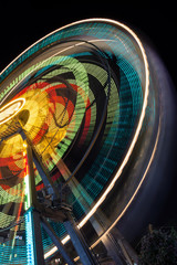 Blurred part of a Ferris wheel at night  with changing colors. Ride spinning, creating light streaks at night