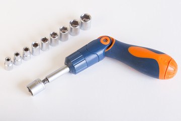 Top view of the screwdriver head. A set of heads and a screwdriver on a light background. Screwdriver with blue - orange handle and a set of heads under the nut.