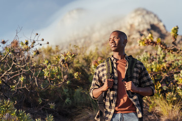 Smiling young African man out for a mountain hike Wall mural