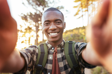 Smiling young African man taking selfies while hiking alone outdoors
