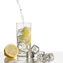 Fototapete - glass full of fresh water with lemon and ice cubes on background