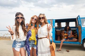 hippie friends near minivan car showing peace sign