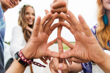 hands of hippie friends showing peace sign