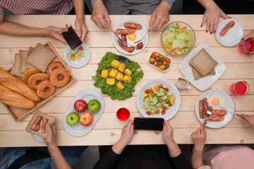 Group of happy smiling friends with smartphones taking picture of food