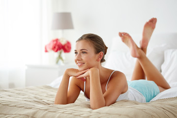 happy young woman lying on bed at home
