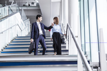 A business couple is talking down the stairs