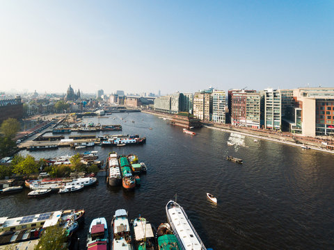 Tourist ships in canal of Amsterdam, aerial view