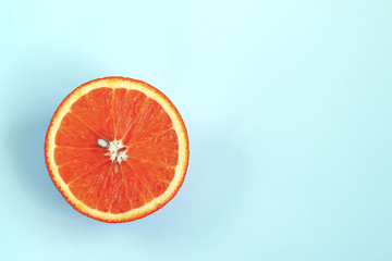 Half of ripe juicy orange on light blue background