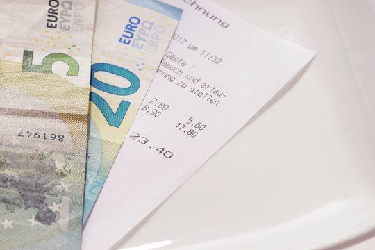 Rechnung und Bargeld auf dem Teller, Trinkgeld inklusive