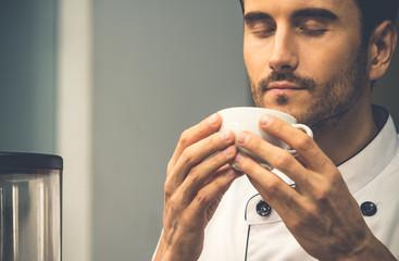 Coffee barista making/drinking coffee, having good smell