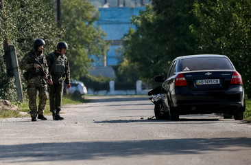 A destroyed car is seen as National Guards patrol in a town of Kalynivka