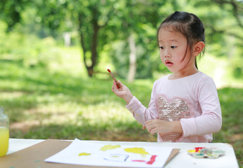 Happy asian child girl sitting at a table in a summer garden painting with paintbrush.