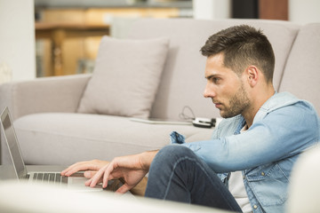 Young man in living-room using laptop computer