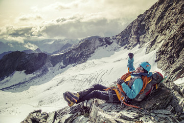 Climber with big smile on his face taking a break and enjoying a view from the mountain top,  with hand raised in the sky