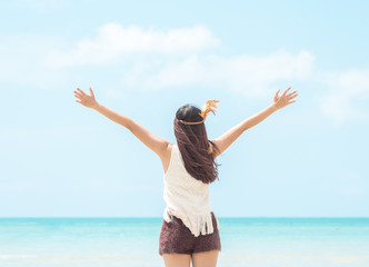 Happy young woman rising hands to sky at sea/beautiful beach, freedom, relaxing on vacation/holiday.