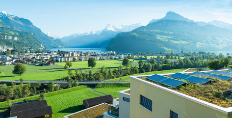 Alps and Lake Lucerne. City Brunnen. Panorama of the canton Schwyz. Residential houses, architecture. In the foreground a roof with solar panels. Small towns of Europe. Switzerland.