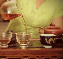 чай в чайниках и чашках стоит на столе