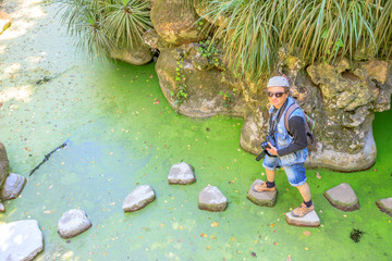 Professional photographer crossing the Lake of the Waterfall in Quinta da Regaleira, Sintra, Portugal.
