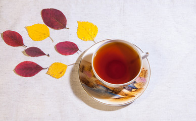 Autumn tea. A cup of tea with autumn leaves. View from above.