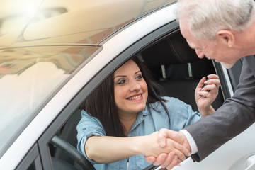 Customer and car salesman shaking hands, light effect