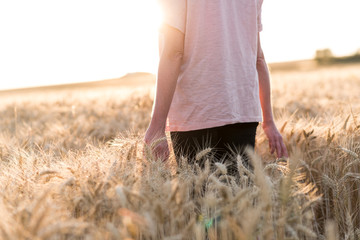 Woman in a wheat field at sunset, sunlight effect